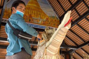 Jeune homme handicapé travaillant sur une statue en feuilles de cocotier