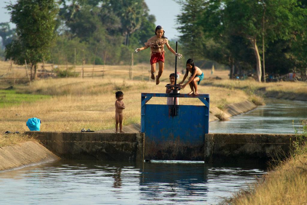 Gamins jouant dans le canal d'irrigation des rizières